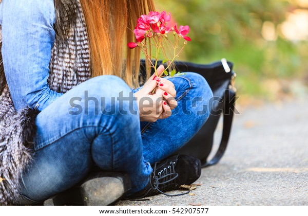 Lifestyle and leisure. Part body woman with beautiful pink flower sitting on ground. Modern fashionable girl wearing jeans clothes spends time on fresh air.