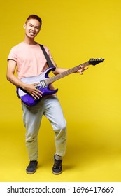 Lifestyle, leisure and youth concept. Vertical portrait of sassy handsome asian man playing electric guitar, smiling pleased, perfoming in band, enjoying jamming, yellow background