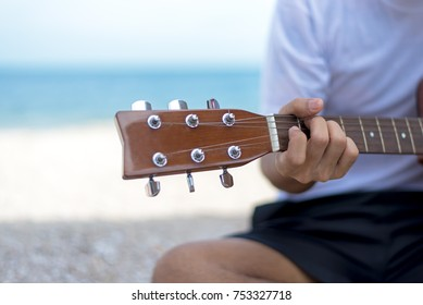 Lifestyle man.  Close up handsome man playing classic guitar sitting on the beach in vacations,summer.  Summer Concept