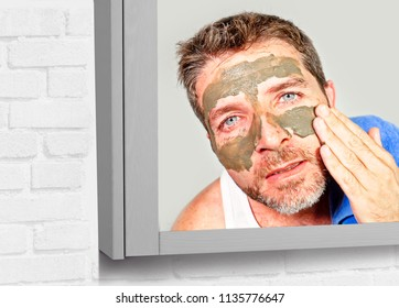 lifestyle mirror portrait of young attractive and happy man with bathroom towel  with green cream on his face applying facial mask in skin care beauty and male cosmetics use concept