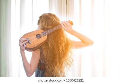 Lifestyle musician with long wavy hair hold ukulele on her back with morning soft light go through the window.Happy charming tender of curly long blond girl musician with ukulele.