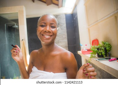 lifestyle natural portrait of young attractive and happy black afro American woman at home bathroom applying face makeup with eyeliner pencil looking on toilet mirror smiling fresh in beauty concept