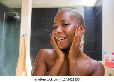 lifestyle natural portrait of young attractive and happy black afro American woman at home bathroom applying face makeup with mascara eyelashes pencil looking on toilet mirror smiling fresh