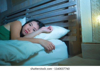 lifestyle night portrait of young beautiful depressed and sad Asian Chinese woman having insomnia lying in bed sleepless suffering anxiety stress and depression problem thinking worried
