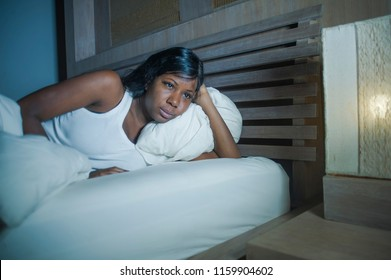 lifestyle night portrait of young sad and worried black african American woman in bed at home sleepless and stressed feeling depressed suffering headache and depression or insomnia sleeping problem