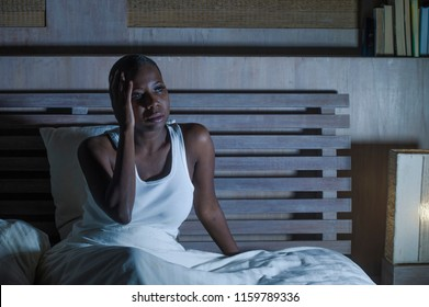 lifestyle night portrait of young scared and stressed black african American woman depressed on bed upset unable to sleep suffering hangover headache feeling sick and scared having nightmare