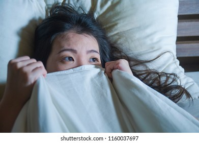 lifestyle night portrait of young scared and stressed Asian Chinese woman lying in bed suffering nightmare in fear and panic grasping blanket covering her horror face expression