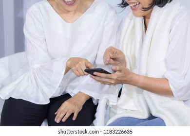 Lifestyle of olld age woman or senior woman colleagues pay attention to new technology use smartphone connect to social media, communication and relax at home / technology lifestyle old age woman