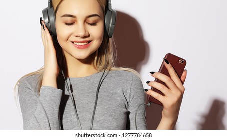 lifestyle and people concept: Beautiful young woman listening to music in headphones on  white background