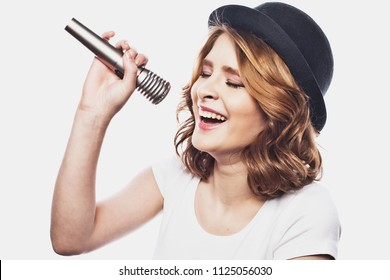 lifestyle and people concept: Beauty model girl singer wearing hat with a microphone