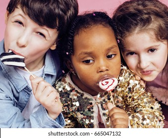 lifestyle people concept: diverse nation children playing together, caucasian boy with african little girl holding candy happy smiling