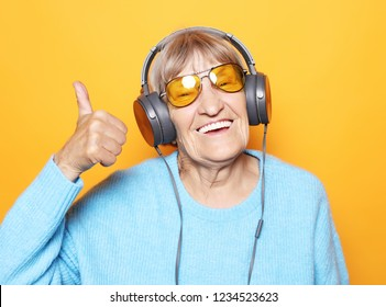 Lifestyle  and people concept: Funny old lady listening music and showing thumbs up. Isolated on yellow background.