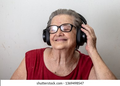 Lifestyle and people concept: Funny old lady listening music and dancing on white background. Elderly woman wearing glasses dancing to music listening on his headphones.