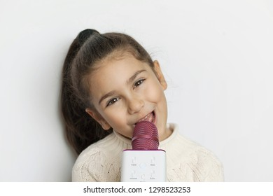 lifestyle and people concept: Happy cute child girl singer with a microphone over white background