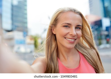 lifestyle and people concept - happy young woman taking selfie on city street