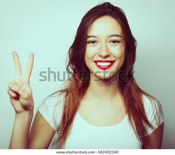 lifestyle and people concept: lovely woman showing victory or peace sign. Special fashion color processing.