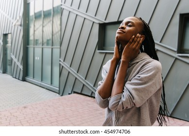 Lifestyle and people concept - smiling african american young woman or teenage girl in headphones listening to music closing ears with her hands outdoors