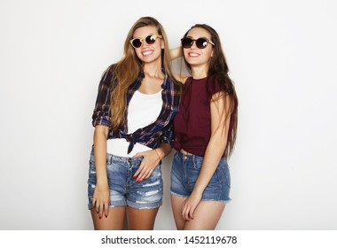 lifestyle and people concept: Two young girl friends standing together and having fun. Hipster style.
