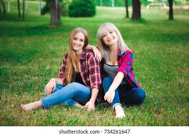 lifestyle and people concept: Two young girl friends sitting together and having fun.