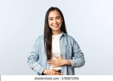 Lifestyle, people emotions and beauty concept. Pleased smiling asian woman rubbing her belly, being full after eating, pleased feeling in stomach from drinking yoghurt