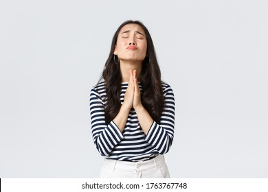 Lifestyle, people emotions and casual concept. Desperate hopeful asian girl making wish, close eyes and hold hands in pray, pleading god to have something, making wishful face, white background
