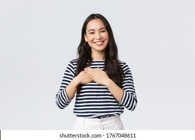Lifestyle, people emotions and casual concept. Touched tender smiling asian woman gladly receive praises, hold hands on heart and grinning thankful, appreciate compliment