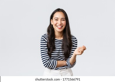 Lifestyle, Menschen Emotionen und flüchtiges Konzept. Sorglos glückliche scheidende Asianin, die Spaß beim Gesprächen mit Menschen hat, lachend und lächelnd optimistisch, stehender weißer Hintergrund fröhlich
