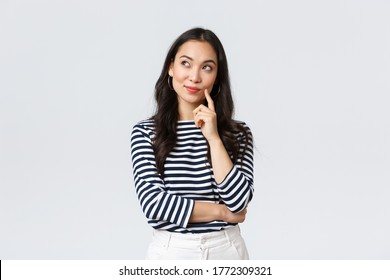 Lifestyle, people emotions and casual concept. Thoughtful stylish young woman smiling pleased, dreaming or imaging perfect plan, have interesting idea, thinking and looking upper left corner