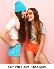 lifestyle, people, teens and friendship concept - happy smiling pretty teenage girls or friends hugging over pink background