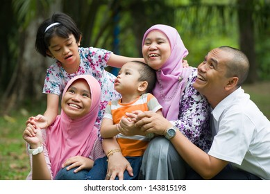 lifestyle photo of malay family having fun in the park ,malaysian people