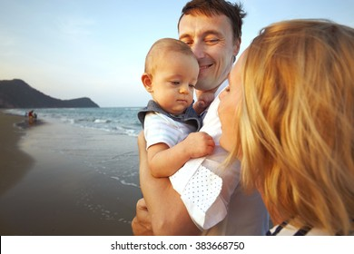 Lifestyle photo normal family with baby boys on the ocean coast