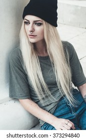 lifestyle photo shoot portrait of cool trendy stylish sexy hipster girl with septum piercing ring. Wearing loose t-shirt, boyfriend jeans and beanie hat.