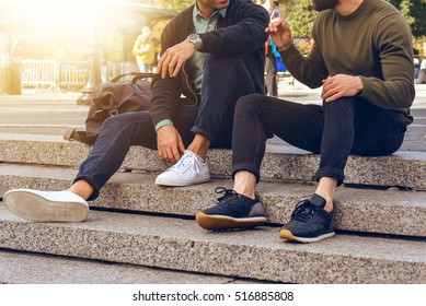 Lifestyle photo of two male friends sitting on the steps in city street and talking wearing casual street style clothes and sneakers.