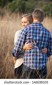 Lifestyle photo of a young Caucasian couple in love hugging each other in tall grass outside