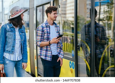Lifestyle photo of young woman and man passengers holds phones waiting while opening door to tram. Portrait of female traveler with backpack talking with handsome guy on tram stop outdoor.