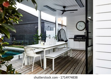 Lifestyle photography of an outdoor poolside patio area in a stylish modern coastal style home, shot late afternoon