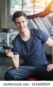 Lifestyle playful man having fun Lifting dumbbell in gym exercise with work out program for health.