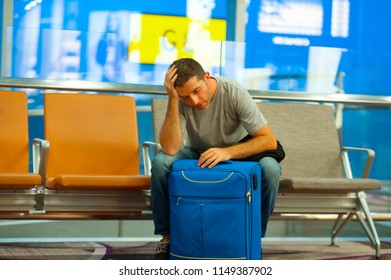 lifestyle portrait in airport of young attractive and tired tourist man with suitcase sitting worried and stressed at boarding gate waiting for cancelled or delayed flight ready for holidays travel