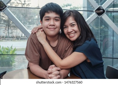 Lifestyle portrait of Asian 40s mother and son, teenage boy hugging and spending time together in an urban cafe