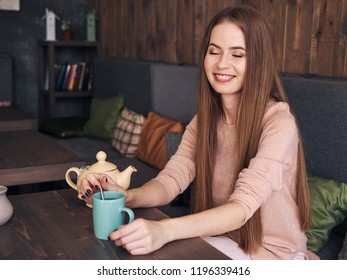 Lifestyle portrait of beautiful cute blonde woman with long hair blue eyes pastel outfit enjoying tea sitting in the cozy cafe near the window with shy smiling