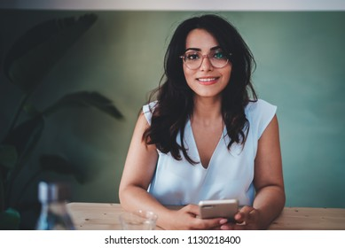 Lifestyle portrait of beautiful hispanic woman in spectacles looks at camera with smile, attractive young businesswoman sitting in coffee shop with modern interior, empty space for text message
