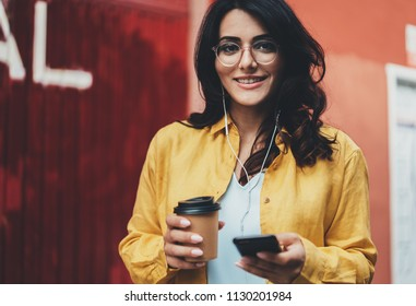 Lifestyle portrait of beautiful woman in trendy look walking outdoor and using modern smartphone device, cute smiling young girl going for a walk in the city park and listening to music in earphones