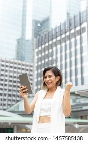 lifestyle portrait beautiful working Asian business woman with feeling happiness in successful using smartphone ,  background with building in city urban