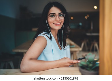 Lifestyle portrait of beautiful young hispanic woman looking at camera while enjoying morning coffee in coffeeshop, happy smiling businesswoman listening to music while  having break in cozy cafe