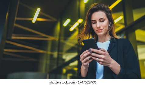 Lifestyle portrait business woman walking in evening city and using mobile gadget, girl banker dressed in business style listen to music wireless earphones and typing text message on smartphone device