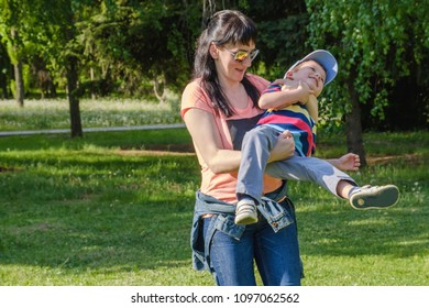 Lifestyle portrait caucasian mother and son in happines at the outside in the meadow