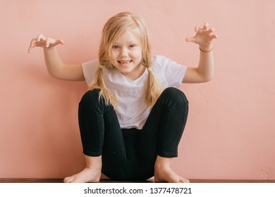 Lifestyle portrait of clowning little girl make faces and shouting on pink wall background. Funny expressive female kid with ridiculous face sitting like monkey with hands apart in scaring pose