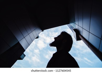 Lifestyle portrait concept. Bearded strolls on the streets of the city among the houses. silhouette portrait in the arch of a modern building close