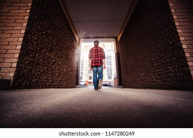 Lifestyle portrait concept. Bearded strolls on the streets of the city among the houses. stroll through the brick arch of the house close