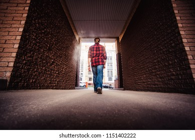 Lifestyle portrait concept. Bearded strolls on the streets of the city among the houses. stroll through the brick arch of the house